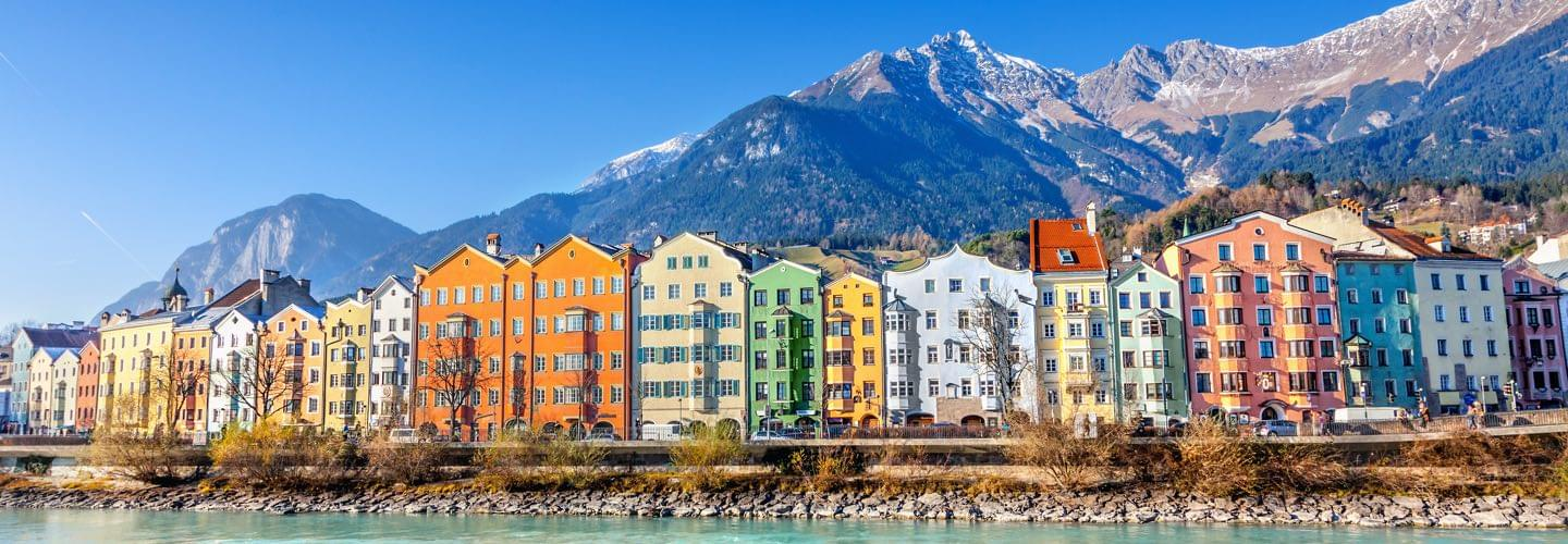 Colourful houses in Innsbruck with the Inn river in foreground and mountains in background