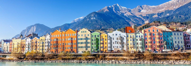 Maisons colorées à Innsbruck avec la rivière Inn au premier plan et les montagnes à l'arrière-plan