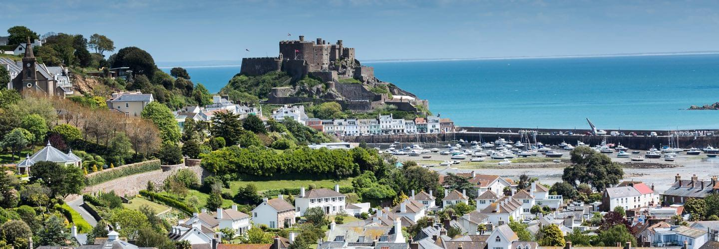 Aerial view of a port in Jersey Island with the Mont Orgueil Castle and the channel in background.