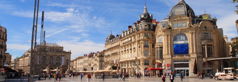 Menschen beim Spaziergang auf dem Place de la Comédie an einem sonnigen Tag in Montpellier.