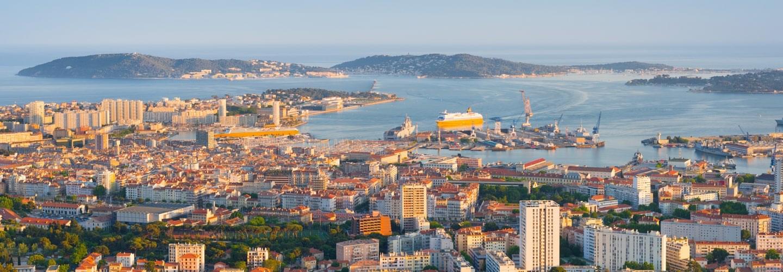 Ville et port de Toulon avec des bateaux de croisière au coucher du soleil avec Saint Mandrier-sur-Mer en arrière-plan.